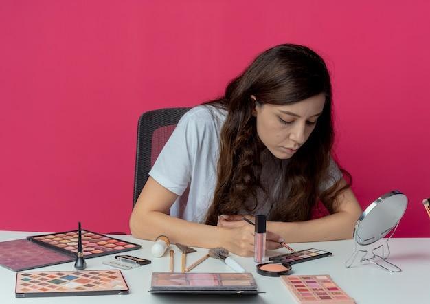 Mooi meisje zit aan de make-up tafel met make-up tools oogschaduw borstel te houden en te kijken naar oogschaduw palet geïsoleerd op crimson achtergrond