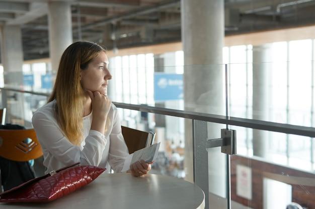 Mooi meisje zit aan tafel met ticket en wacht op vliegtuig
