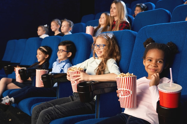 Mooi meisje zit in de bioscoop met vrienden, camera kijken en glimlachen tijdens het kijken naar film. klein schattig afrikaans vrouwelijk kind dat popcorn eet en zoet water drinkt