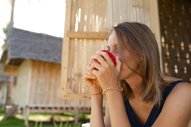 Mooi meisje zit in de buurt van de bungalow en drinkt koffie.