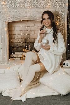 Mooi meisje zit in de buurt van open haard en houdt een kerststuk speelgoed