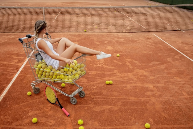 Mooi meisje zit in de mand van tennisballen terwijl ze tennisballen en racket in haar hand houdt.