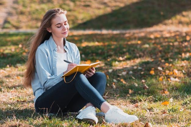 Mooi meisje zit in de natuur en schrijven