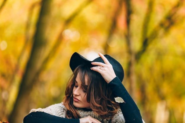 Mooi meisje zit in een park en maakt haar hoed glad