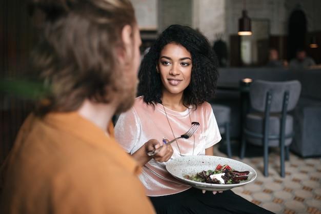 Mooi meisje zit in restaurant met vriend. lachende afro-amerikaanse dame zit in café met plaat van salade in de hand