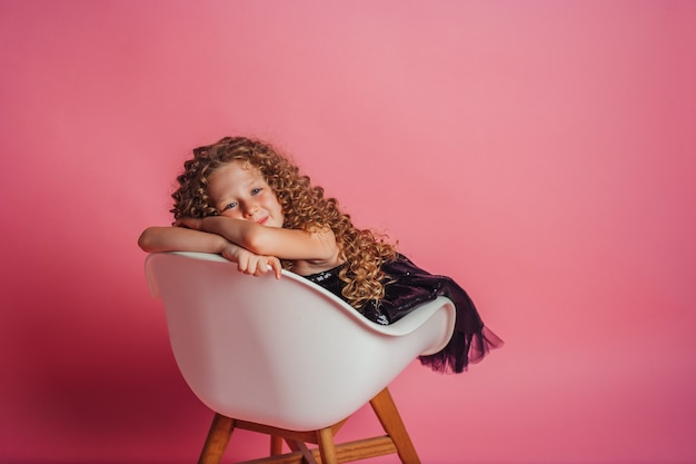 Mooi meisje zit in zwarte jurk op roze achtergrond in studio