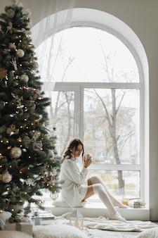 Mooi meisje zit met een kopje thee en plaid in de buurt van een kerstboom