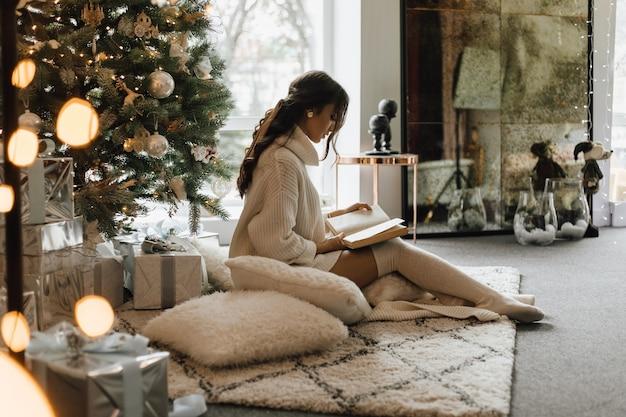 Mooi meisje zit met kussens en plaid in de buurt van een kerstboom en een boek te lezen