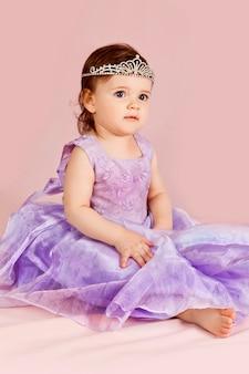 Mooi meisje zit met tiara, paarse jurk op roze