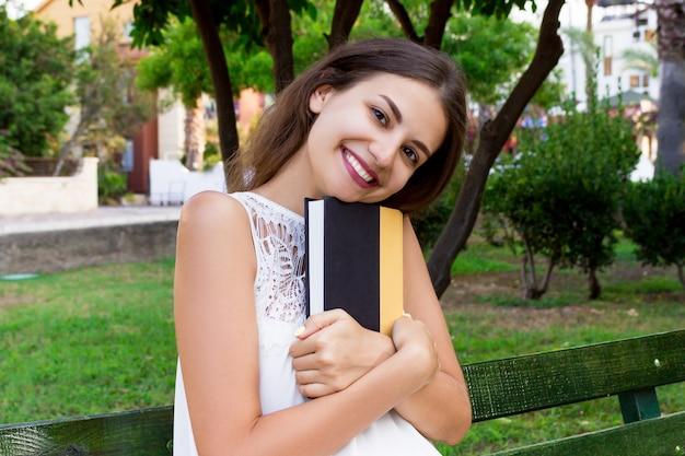 Mooi meisje zit op de bank in het park en knuffelt een boek.