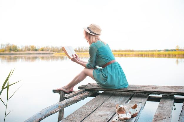 Mooi meisje zit op een houten brug en leest een boek.