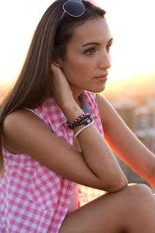 Mooi meisje zit op het dak bij zonsondergang.
