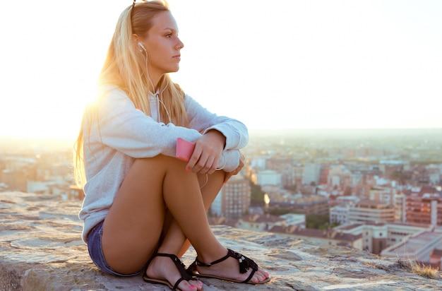 Mooi meisje zit op het dak en luisteren naar muziek.