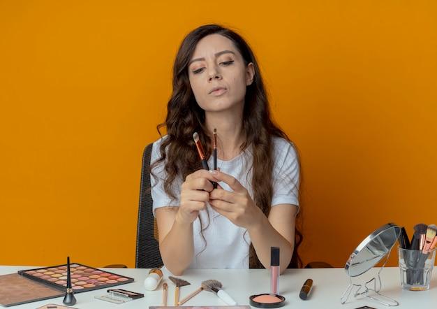 Mooi meisje, zittend aan de make-up tafel met make-up tools houden en kijken naar concealer en oogschaduw borstels geïsoleerd op een oranje achtergrond