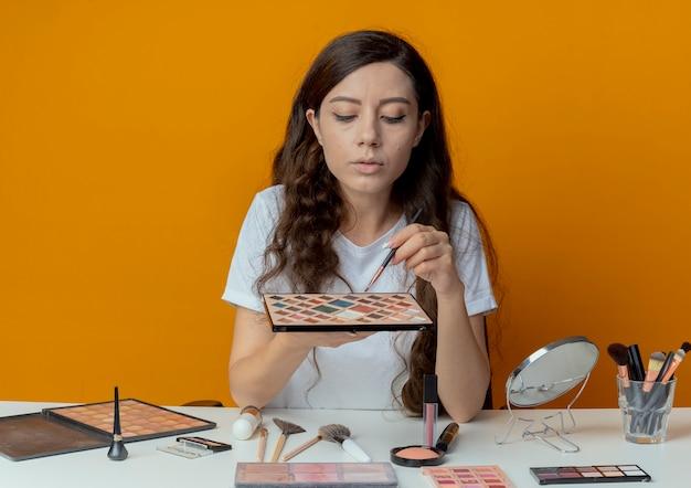 Mooi meisje zittend aan de make-up tafel met make-up tools oogschaduw palet en penseel te houden en te kijken naar hen geïsoleerd op een oranje achtergrond