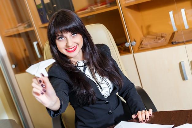 Mooi meisje, zittend aan een bureau in het kantoor en lanceert een papieren vliegtuigje