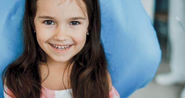 Mooi meisje zittend in de stoel stomatologie na een tandonderzoek.