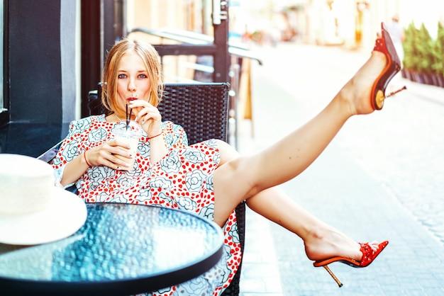 Mooi meisje, zittend in de straat café met koud drankje