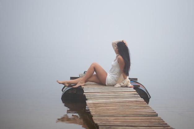 Mooi meisje zittend op de pier bij de rivier