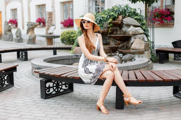 Mooi meisje, zittend op een bankje in een zonnige zomerdag.