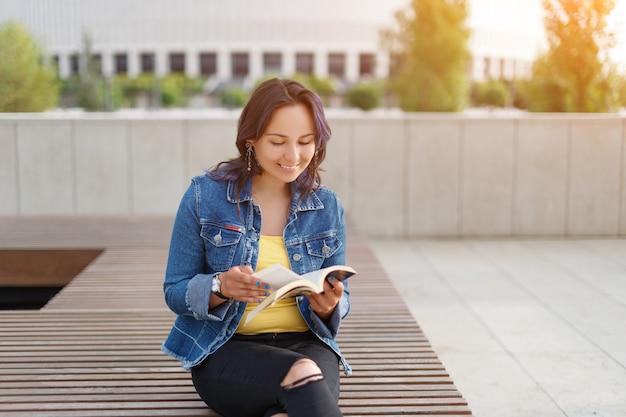 Mooi meisje zittend op een bankje in het park, een boek lezen en glimlachen