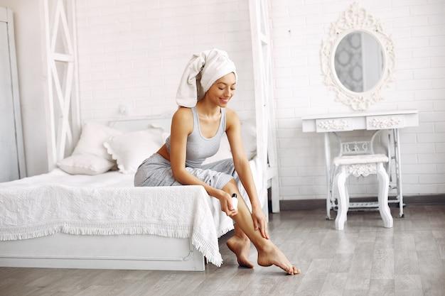 Mooi meisje, zittend op een bed met schoonheidsproducten