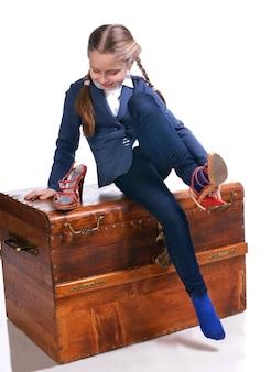 Mooi meisje zittend op een grote doos en moeders schoenen proberen
