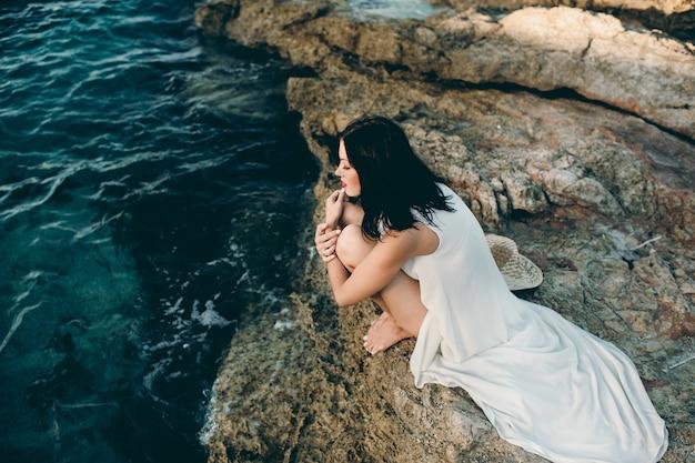 Mooi meisje, zittend op een rots op het strand zee