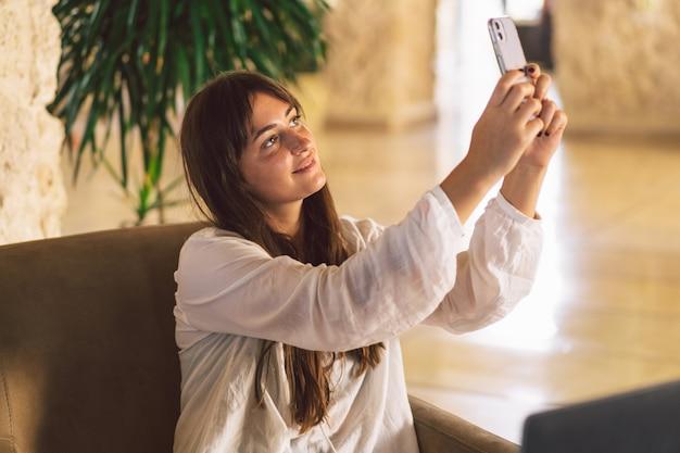 Mooi meisje, zittend op een stoel en spreekt via video-oproep aan de telefoon