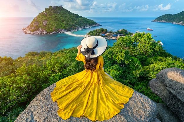 Mooi meisje zittend op gezichtspunt op het eiland koh nangyuan in de buurt van het eiland koh tao, surat thani in thailand