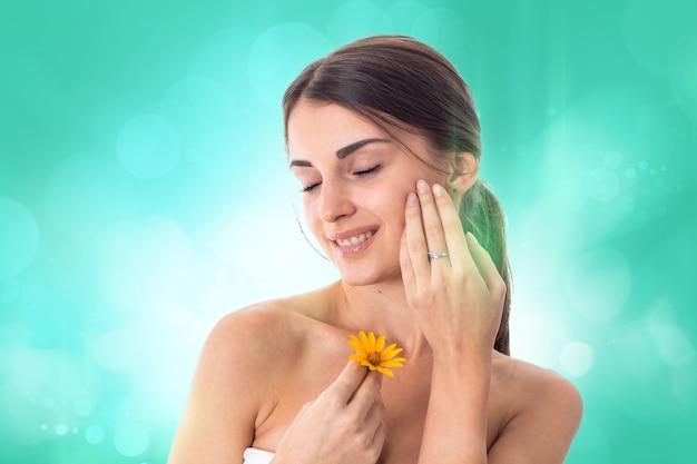 Mooi meisje zorgt voor haar huid met gele bloem in handen geïsoleerd op een witte achtergrond. gezondheidszorgconcept. lichaamsverzorgingsconcept. jonge vrouw met een gezonde huid.