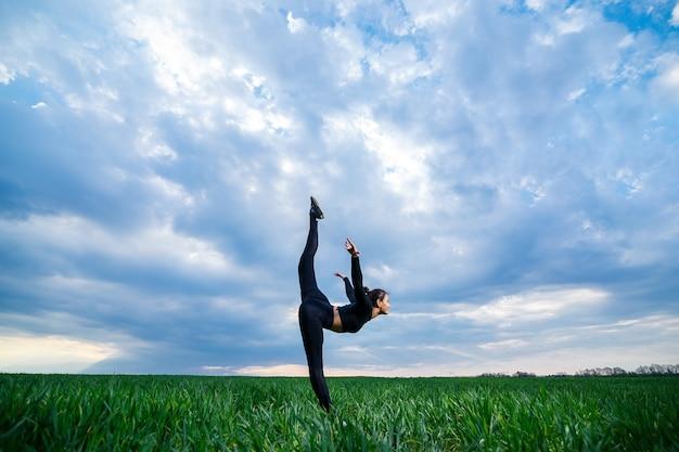 Mooi meisjesmodel op groen gras doet yoga. een mooie brunette op een groen gazon voert acrobatische elementen uit. flexibele turnster in het zwart doet oefeningen