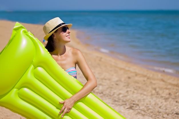 Mooi meisjesportret met opblaasbare vlottermatras op de achtergrond van de strandzomer met exemplaarruimte