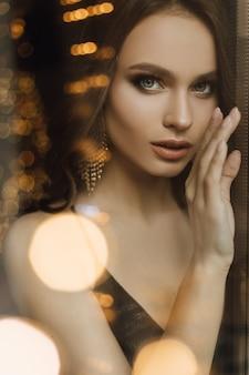 Mooi meisjesportret op slingerlichten Gratis Foto