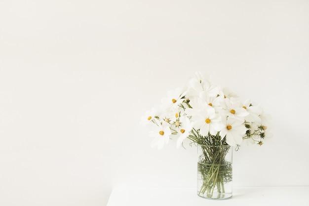 Mooi met witte kamille, madeliefjebloemen in vaas die zich op witte lijst bevindt