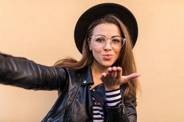 Mooi mode meisje in leren jas en zwarte hoed geeft luchtkus geïsoleerd op lichtgele muur