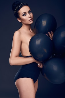 Mooi mode naakt modelmeisje met zwarte ballons