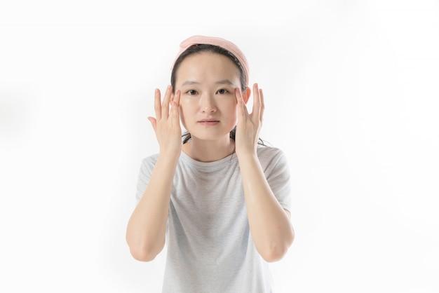Mooi model dat kosmetische roombehandeling op haar gezicht op wit toepast