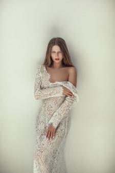 Mooi model draagt witte kanten jurk poseren in een lichte kamer