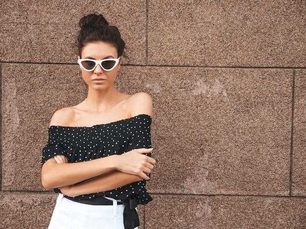 Mooi model gekleed in elegante zomer kleding. sexy zorgeloos meisje poseren in de straat in de buurt van muur. trendy moderne zakenvrouw in zonnebril plezier