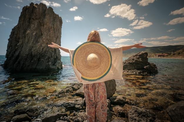 Mooi model in boho-stijl met witte top en sombrero die zich voordeed op het strand in zonlicht