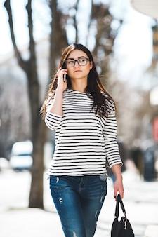 Mooi model in een gestreepte trui en praat aan de telefoon.