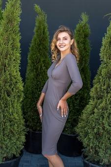 Mooi model in grijze jurk naar de natuur, zomertijd