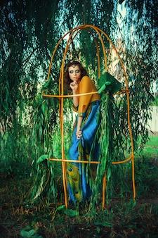 Mooi model is poseren in een kleurrijke pauw jurk