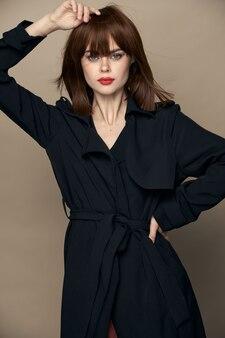 Mooi model klassieke jas lichte make-up poseren op een geïsoleerde ruimtelevensstijl
