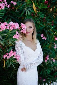 Mooi model meisje, met bloemen pioen in de buurt van het gezicht. cosmetica, schoonheid, make-up, bruiloft en cosmetologie.