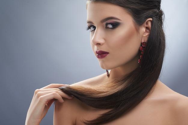 Mooi model met een mooi kapsel en avondmake-up: ze draagt bordeauxrode lippenstift, zwarte eyeliner en gouden markeerstift. ook draagt ze lange oorbellen.