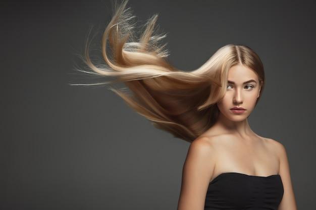 Mooi model met lang glad, vliegend blond haar dat op donkergrijze studioachtergrond wordt geïsoleerd. jong kaukasisch model met goed onderhouden huid en haren die in de lucht blazen.