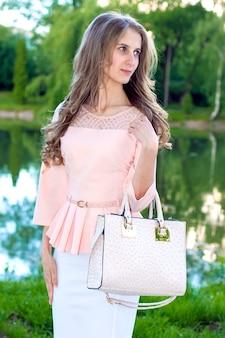 Mooi model met lang krullend haar met een handtas op zonnige dag