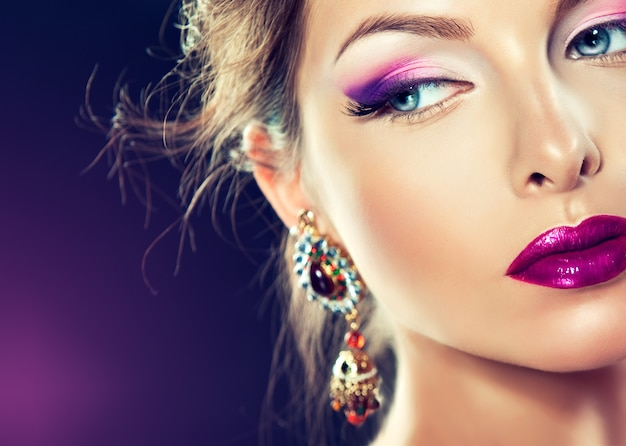 Mooi model met modieuze make-up en paarse manicure op de nagels van sierlijke vingers. heldere avondmake-up, met de paarse oogleden en lippen.